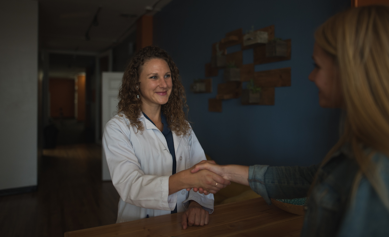 carol shaking hands and smiling with a patient