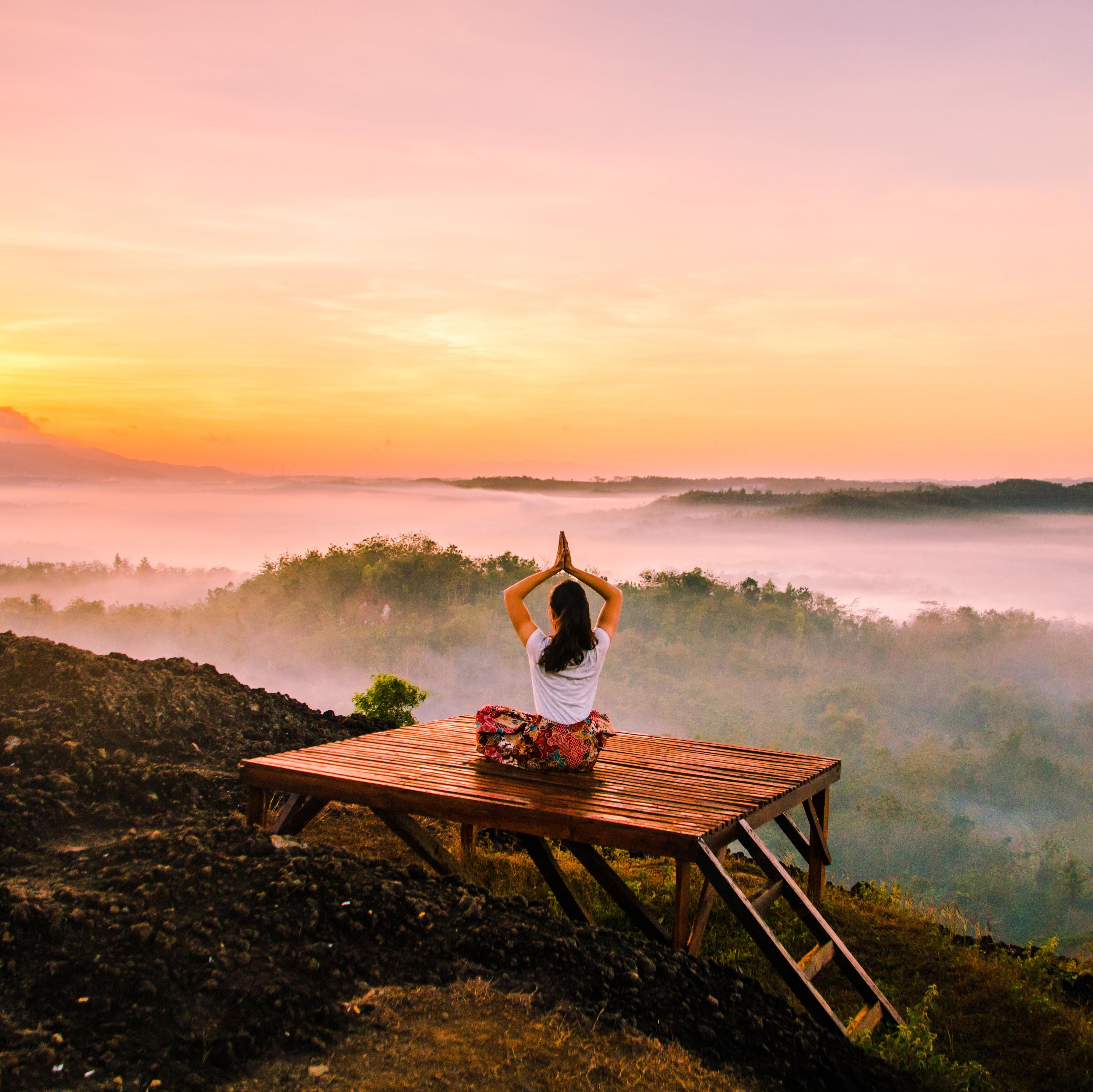 a woman doing yoga at sunrise outside