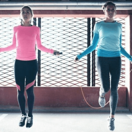 two woman jumping ropes as they work out