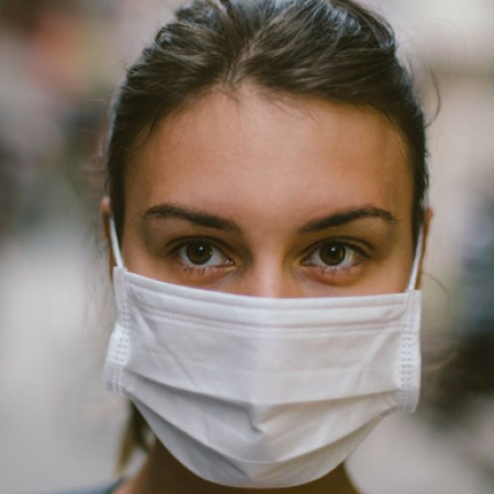 a woman is wearing a white surgical mask
