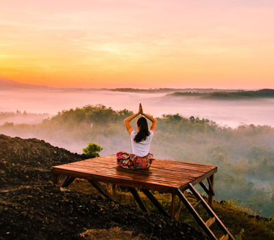 a woman is doing yoga on a field during sunrise
