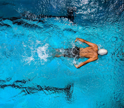 a man is doing laps in a swimming pool