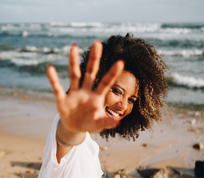 a woman is holding her hand in front of the camera as she smiles in front of a beach