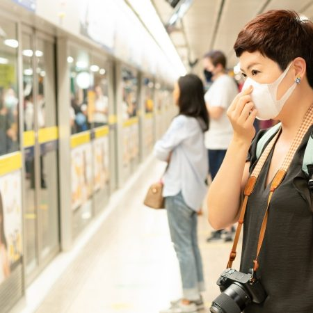 a woman wearing a mask is waiting on a train platform