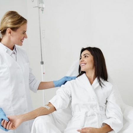 a woman with black hair wearing a white rob is sitting down and smiling at the nurse who is holding her arm that has IV