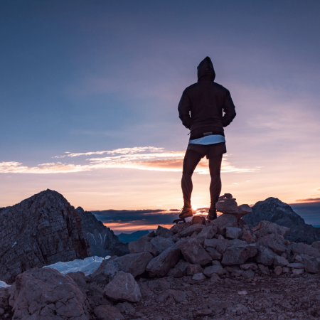 a man with his hoodie on is standing on top of a mountain overlooking a setting sun. His back is turned towards the camera.