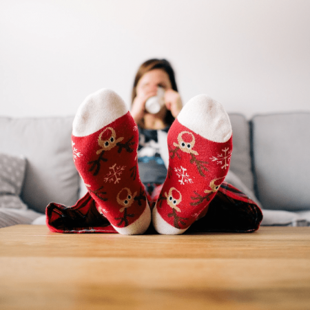 a woman is sitting on a grey couch and drinking from a coffee mug. She has her feet on the wooden coffee table and is wearing decorative reindeer socks.