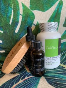 there are three bottles for PRP hair restoration and a wooden hairbrush in front of a green leaves background.